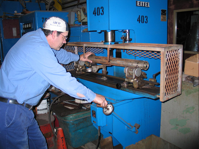 Overbend straightening of machine spindle using 20-ton hydraulic press.