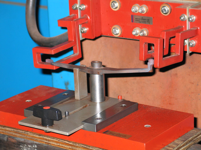 Induction heating: hardening both ends of machine gun ammunition belt tension lever.